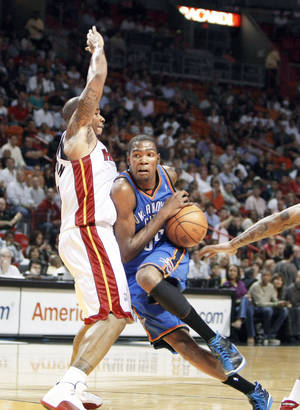 Photo - The Thunder's Kevin Durant drives around the Heat's Quentin Richardson on Tuesday in Miami. AP photo