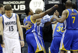 Photo - Golden State Warriors players celebrate at the buzzer as a dejected Minnesota Timberwolves' Luke Ridnour, left, leaves the court after Golden State won 100-99 in  an NBA basketball game Sunday, Feb. 24, 2013, in Minneapolis. (AP Photo/Jim Mone)
