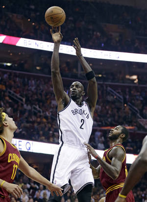 Photo - Brooklyn Nets' Kevin Garnett , center, shoots over Cleveland Cavaliers' Anderson Varejao, left, of Brazil, and Earl Clark during the first quarter of an NBA basketball game Wednesday, Oct. 30, 2013, in Cleveland. (AP Photo/Tony Dejak)