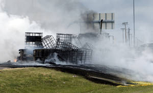 Photo - A massive fire on a northbound semi trailer loaded with roadway paint shut down Interstate 35 both north and southbound at around 6:45 p.m. on Wednesday, July 10, 2013 in Norman, Okla.  Photo by Steve Sisney, The Oklahoman <strong>STEVE SISNEY - THE OKLAHOMAN</strong>