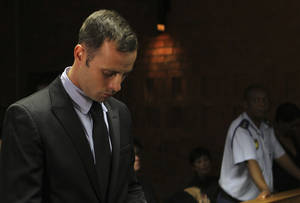 "photo - Olympic athlete Oscar Pistorius stands inside the court as a police officer looks on during his bail hearing at the magistrate court in Pretoria, South Africa, Wednesday, Feb. 20, 2013. A South African judge says defense lawyers will need to offer ""exceptional"" reasons to convince him to grant bail for Oscar Pistorius, when a hearing resumes Wednesday. (AP Photo/Themba Hadebe)"