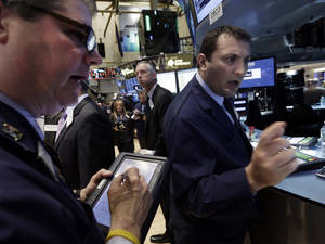 Photo - Specialist Vincent Surace, right, works at his post on the floor of the New York Stock Exchange, Friday, May 2, 2014. U.S. stock futures are up slightly after the U.S. unemployment rate hit its lowest level in more than five years. The government reported the unemployment rate sank to 6.3 percent. (AP Photo/Richard Drew)