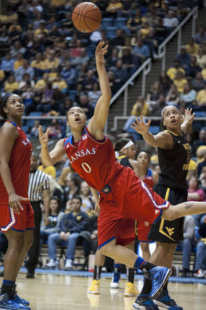 Photo - Kansas' Asia Boyd (0) drives to the basket during the first half of an NCAA college basketball game against West Virginia, Tuesday, March 4, 2014, in Morgantown, W.Va. (AP Photo/Andrew Ferguson)