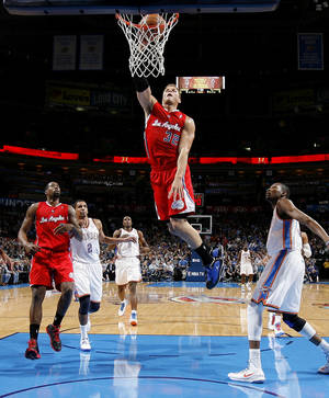 photo - The Clippers Blake Griffin (32) dunks the ball as Oklahoma City&#039;s Kevin Durant (35) and Thabo Sefolosha (2) watch during an NBA basketball game between the Oklahoma City Thunder and the Los Angeles Clippers at Chesapeake Energy Arena in Oklahoma City, Wednesday, Nov. 21, 2012. Photo by Bryan Terry, The Oklahoman
