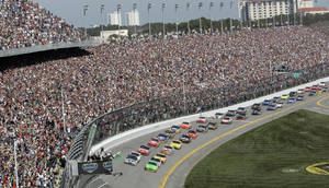 photo - FILE - In this Feb. 14, 2010, file photo, drivers take the green flag for the start of the NASCAR Daytona 500 auto race at Daytona International Speedway in Daytona Beach, Fla. Daytona International Speedway president Joie Chitwood announced, on Tuesday, Jan. 22, 2013, a proposed multi-year redevelopment of the historic racetrack.  The plan includes five new modern entrances, a second pedestrian bridge for easier access to the track and an expanded grandstand area with thousands of more seats.  (AP Photo/David Graham, File)