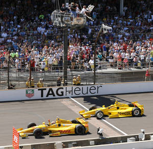 Photo - Ryan Hunter-Reay celebrates after crossing the finish line take the checkered flag in front of Helio Castroneves, of Brazil, to win the 98th running of the Indianapolis 500 IndyCar auto race at the Indianapolis Motor Speedway in Indianapolis, Sunday, May 25, 2014. (AP Photo/Dave Parker)