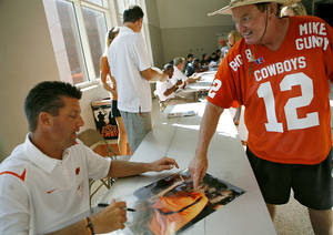 photo - Oklahoma State football coach Mike Gundy signs an autograph for Cowboys fan Gayle Stone, of Woodward, during OSU's Fan Appreciation Day on Saturday at Gallagher-Iba Arena in Stillwater. (Photo by John Clanton, The Oklahoman)