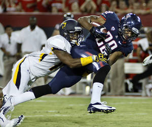 Photo -   Arizona's Austin Hill (29) tries to break the tackle of Toledo's Cheatham Norrils, left, during the first half of an NCAA college football game at Arizona Stadium in Tucson, Ariz., Sat., Sept. 1, 2012. (AP Photo/Wily Low)