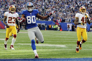 photo -   New York Giants' Victor Cruz scores the winning touchdown ahead of Washington Redskins' DeAngelo Hall (23) and Madieu Williams (41) during the fourth quarter of an NFL football game, Sunday, Oct. 21, 2012, in East Rutherford, N.J. The Giants won 27-23. (AP Photo/The Record of Bergen County, Tyson Trish) MAGS OUT; TV OUT; NO ARCHIVING; MANDATORY CREDIT