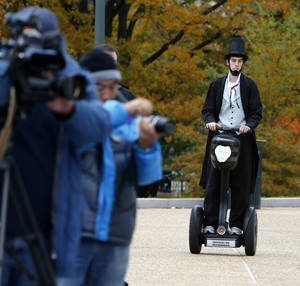 "Photo -   As members of the media, left, wait, Christopher Brady, dressed as Abraham Lincoln, arrives on a Segway at the launching ceremony of the Lincoln Movie Trail at the State Capitol in Richmond, Va. Thursday, Nov. 15, 2012. With Steven Spielberg's ""Lincoln"" set for national release Friday, Virginia tourism officials are inviting fans of history and film to tour the locations where the epic movie was made. (AP Photo/Richmond Times-Dispatch, Bob Brown)"