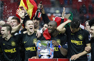Photo - FILE - In this Saturday, May 11, 2013 file photo, Wigan Athletic players including their captain Emmerson Boyce, centre right, celebrate after their 1-0 win over Manchester City in their English FA Cup final soccer match at Wembley Stadium, London. Wigan Athletic hadn't won a piece of major silverware in its 81-year history until last May, when it pulled off one of the great FA Cup upsets by beating big-spending Manchester City in the final. Now, despite dropping out of the Premier League at the end of last season, it is on course to retain the famous trophy against all the odds. (AP Photo/Jon Super, File)