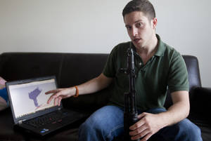 "Photo - In this Oct. 3, 2012 photo, ""Wiki Weapons"" project leader Cody Wilson points to his laptop screen displaying an image of a prototype plastic gun on the screen, while holding in his other a weapon he calls ""Invivdual Mandate,"" in Austin, Texas. At least one group, called Defense Distributed, is claiming to have created downloadable weapon parts that can be built using the increasingly popular new-generation of printer that utilizes plastics and other materials to create 3-D objects with moving parts. Wilson says the group last month test fired a semiautomatic AR-15 rifle _ one of the weapon types used in the Connecticut elementary school massacre _ which was built with some key parts created on a 3-D printer. The gun was fired six times before it broke. (AP Photo/Statesman.com, )  MAGS OUT; NO SALES; INTERNET AND TV MUST CREDIT PHOTOGRAPHER AND STATESMAN.COM"