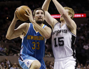 Photo - New Orleans Hornets' Ryan Anderson (33) drives past San Antonio Spurs' Matt Bonner (15) during the first quarter of an NBA basketball game, Wednesday, Jan. 23, 2013, in San Antonio. (AP Photo/Eric Gay)