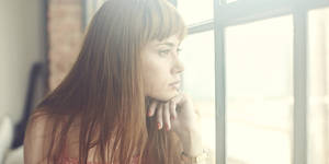Photo - Young Woman looking out of window