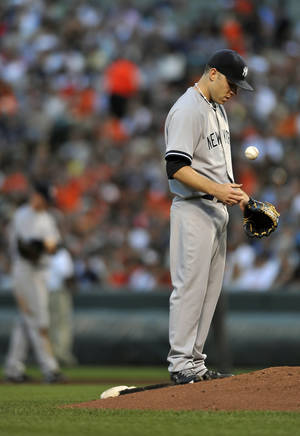 Photo - New York Yankees pitcher David Phelps pauses as he tosses the ball during the third inning of a baseball game against the Baltimore Orioles, Saturday, June 29, 2013, in Baltimore. (AP Photo/Gail Burton)