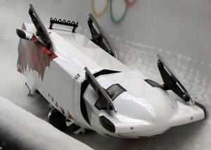 Photo - The team from Canada CAN-3, with Justin Kripps, Jesse Lumsden, Cody Sorensen and Ben Coakwell, slide down the track upside down after crashing in turn sixteen during the men's four-man bobsled competition at the 2014 Winter Olympics, Saturday, Feb. 22, 2014, in Krasnaya Polyana, Russia. (AP Photo/Dita Alangkara)