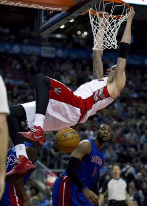 Photo - Toronto Raptors center Jonas Valanciunas slams a dunk over Detroit Pistons center Andre Drummond (1) during the first half of an NBA basketball game in Toronto on Monday, April 1, 2013. (AP Photo/The Canadian Press, Frank Gunn)