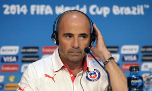 Photo - Chile's head coach Jorge Sampaoli holds his translator headphone during a press conference the day before the group B World Cup soccer match between Chile and Australia in the Arena Pantanal in Cuiaba, Brazil, Thursday, June 12, 2014. (AP Photo/Michael Sohn)
