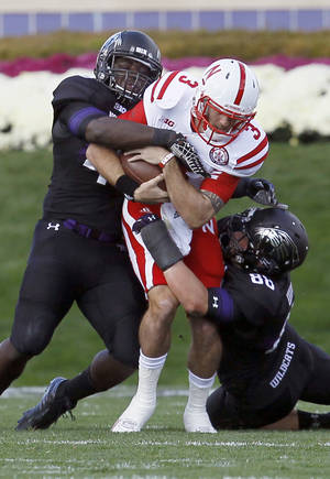 Photo -   Nebraska quarterback Taylor Martinez (3) is sacked by Northwestern Wildcats linebacker Damien Proby (46), left, and defensive lineman Quentin Williams (88) during the first half of an NCAA college football game on Saturday, Oct. 20, 2012, in Evanston, Ill. (AP Photo/Charles Rex Arbogast)