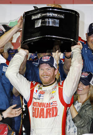 Photo - Dale Earnhardt Jr. raises the trophy in Victory Lane after winning the NASCAR Daytona 500 Sprint Cup series auto race at Daytona International Speedway in Daytona Beach, Fla., Sunday, Feb. 23, 2014. (AP Photo/Terry Renna)