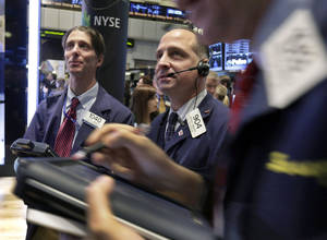 photo - In this Tuesday, Jan. 8, 2013, photo, Traders Todd Ingrilli, left, and Michael Urkonis, center, work on the floor of the New York Stock Exchange. World stock markets rose Wednesday after the fourth-quarter earnings season got off to a positive start in the U.S. with aluminum giant Alcoa forecasting higher demand for 2013. (AP Photo/Richard Drew)