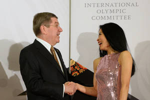 Photo - In this photo taken on Thursday, Feb. 6, 2014, International Olympic Committee President Thomas Bach, left, shares a laugh with former musician Vanessa-Mae, who will compete for Thailand as alpine skier Vanessa Vanakorn before the IOC President's Gala Dinner on the eve of the opening ceremony of the 2014 Winter Olympics, in Sochi, Russia. As a violin virtuoso, Vanessa-Mae has been endearing herself to large audiences since she was a small child. Because of her flourishing musical career, skiing has played always second fiddle. At the Sochi Winter Games, that tune will change. The classical-pop musician is set to compete for Thailand in the Olympic giant slalom on Tuesday, Feb. 18. (AP Photo/Andrej Isakovic, Pool)