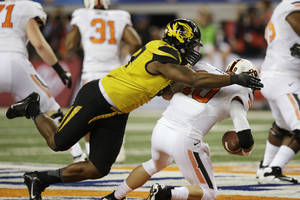 Photo - Missouri defensive lineman Kony Ealy, left, sacks Oklahoma State quarterback Clint Chelf (10) during the first half of the Cotton Bowl NCAA college football game on Friday, Jan. 3, 2014, in Arlington, Texas. (AP Photo/Tim Sharp)
