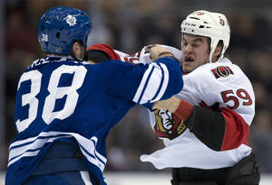photo - Toronto Maple Leafs left winger Fraser McLaren (38) knocks out Ottawa Senators left winger Dave Dziurzynski during a fight in first-period NHL hockey game action in Toronto, Wednesday, March 6, 2013. (AP Photo/The Canadian Press, Frank Gunn)