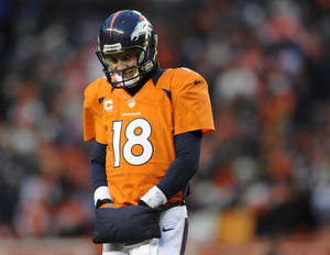 Photo - Denver Broncos quarterback Peyton Manning walks off the field after fumbling the ball against the Baltimore Ravens in the third quarter of an AFC divisional playoff NFL football game, Saturday, Jan. 12, 2013, in Denver. (AP Photo/Jack Dempsey)
