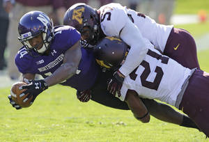 Photo - Minnesota defensive back Brock Vereen (21) and linebacker Aaron Hill (57) tackle Northwestern wide receiver Christian Jones (14) during the first half of an NCAA college football game in Evanston, Ill., Saturday, Oct. 19, 2013. (AP Photo/Nam Y. Huh)