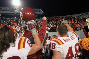 Photo - Iowa State players celebrate their overtime win in front of their fans section during their NCAA college football game against West Virginia in Morgantown, W.Va., on Saturday, Nov. 30, 2013. Iowa State won 52-44 in the third overtime. (AP Photo/Christopher Jackson)