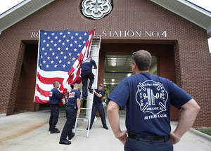 Photo -   Capt. Kris Small of the Rock Hill, S.C. Fire Department watches as other Rock Hill firefighters put a giant American Flag on the front of Station 4 on Tuesday, Sept. 11. 2012 to commemorate Sept. 11 terrorist attacks. (AP Photo/ The Herald, Andy B urriss)