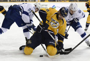 Photo - Tampa Bay Lightning right wing Nikita Kucherov (86), of Russia, Nashville Predators forward Paul Gaustad (28) and Lightning center Tyler Johnson (9) battle for the puck in the first period of an NHL hockey game, Thursday, Feb. 27, 2014, in Nashville, Tenn. (AP Photo/Mark Zaleski)