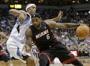 Photo - Miami Heat forward LeBron James (6) drives against Minnesota Timberwolves forward Dante Cunningham, left, during the second quarter of an NBA basketball game in Minneapolis, Saturday, Dec. 7, 2013. (AP Photo/Ann Heisenfelt)