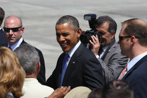 Photo - President Barack Obama is greeted upon his arrival at the Orlando International Airport in Orlando, Fla., Thursday, March 20, 2014, enroute to the Valencia Community College West campus to speak about the role of women in the U.S. economy. (AP Photo/Alex Menendez)