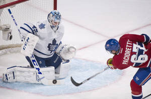 Photo - Toronto Maple Leafs goaltender Jonathan Bernier, left, makes a save against Montreal Canadiens' Max Pacioretty (67) during first-period NHL hockey game action in Montreal, Saturday, March 1, 2014. (AP Photo/The Canadian Press, Graham Hughes)