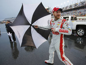 Photo - Dale Earnhardt Jr. opens his umbrella as he heads to the garages during a rain delay at the NASCAR Sprint cup Series auto race at Daytona International Speedway in Daytona Beach, Fla., Saturday, July 5, 2014. (AP Photo/Terry Renna)