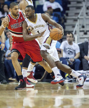 Photo - New Orleans Pelicans forward Tyreke Evans (1) dribbles around Portland Trail Blazers forward Nicolas Batum (88) in the first half of an NBA basketball game in New Orleans, Friday, March 14, 2014. (AP Photo/Scott Threlkeld)