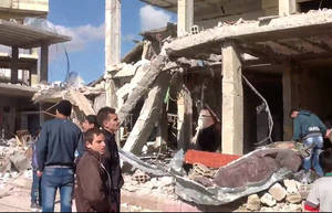 Photo - In this photo released by the Syrian official news agency SANA, Syrian citizens gather in front of a damaged building destroyed by a car bomb in Qatana, (25) kilometers (15 miles) southwest of Damascus, Syria, Thursday, Dec. 13, 2012. A bomb blast near a school in a Damascus suburb killed more than a dozen people, at least half of them women and children, the state news agency reported. Russia, Syria's most important international ally, said for the first time that President Bashar Assad is increasingly losing control and the opposition may win the civil war. (AP Photo/SANA)