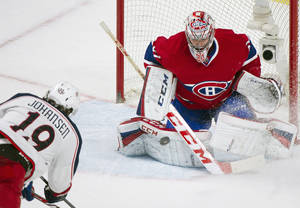 Photo - Columbus Blue Jackets' Ryan Johansen, left, scores against Montreal Canadiens goaltender Carey Price during the third period of an NHL hockey game in Montreal, Thursday, March 20, 2014. (AP Photo/The Canadian Press, Graham Hughes)