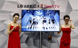 """Photo - FILE - In this Thursday, Jan. 19, 2012, file photo, South Korean models pose with a CINEMA 3D Smart TV during a press conference to introduce the LG Electronics' television and the company's marketing strategy for 2012 in Seoul, South Korea.  Hewlett-Packard said Monday, Feb. 25, 2013,  it is selling its webOS operating system technology to South Korea's LG Electronics Inc. for an undisclosed sum. Hewlett Packard Co. and LG said on Monday that LG will use webOS to support its """"smart TV"""" technology. (AP Photo/Ahn Young-joon)"""