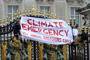"Photo -   Protesters from the Climate Siren group hang a banner from the gates of Buckingham Palace, London Saturday June 23, 2012. Police say four climate change activists scaled the gates of Queen Elizabeth II's Buckingham Palace home and locked themselves to railings. The group, from the Climate Siren group, wore T-shirts with the slogan ""Climate emergency. 10% annual emission cuts."" (AP Photo/Rebecca Naden/PA Wire) UNITED KINGDOM OUT"