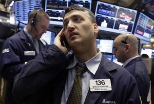 Photo - Trader Nicholas DeStafano, center, works on the floor of the New York Stock Exchange Wednesday, Feb. 5, 2014. The U.S. stock market is edging lower in early trading after a modest recovery the day before. (AP Photo/Richard Drew)