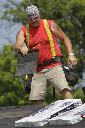 Photo - <p>Construction worker Tony Elshoff installs roofing tile in 100 degree temperatures Tuesday, July 17, 2012 in Springfield, Ill. Along with the unrelenting heat wave, the nation's widest drought in decades is spreading. More than half of the continental U.S. is now in some stage of drought, and most of the rest is abnormally dry. (AP Photo/Seth Perlman)</p>