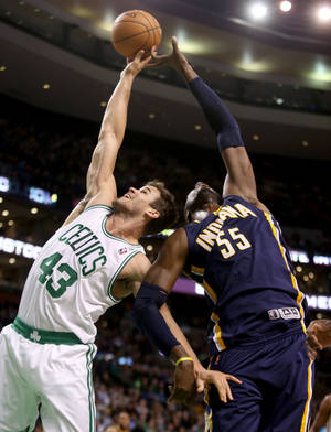Photo - Boston Celtics center Kris Humphries (43) and Indiana Pacers center Roy Hibbert (55) vie for a rebound during the first half of an NBA basketball game on Saturday, March 1, 2014, in Boston. (AP Photo/Mary Schwalm)