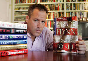 "Photo - FILE - In a Sept. 2, 2005 file photo, best-selling author Vince Flynn poses with the dust jacket of his new book, ""Consent to Kill,"" and copies of his six other books in his home in Edina, Minn. Flynn died, Wednesday, June 18, 2013, after a two-year battle with prostate cancer, a statement from Flynn's publisher, Simon & Schuster, Inc., said. He was 47. (AP Photo/Jim Mone, File)"