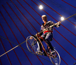 Photo - Circus performer Jim Decker uses a 19 foot pole to balance himself on a bicycle as he rides across a tightrope stretched 20 feet above the ground during the Zoppe Italian Family Circus at the Oklahoma State Fair on Wednesday, , Sep. 18, 2013. Photo  by Jim Beckel, The Oklahoman.