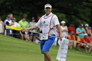 Photo - FILE - In this July 4, 2013, file photo, New Orleans Saints coach Sean Payton carries the flag for golfer Ryan Palmer on the eighth hole during the first round of the Greenbrier Classic PGA tour golf tournament at the Greenbrier in White Sulphur Springs, W.Va. The Saints announced Thursday, March 13, 2014, that the team will split their 2014 training camp between the team's practice facility in Metarie, La., and The Greenbrier in White Sulphur Springs. (AP Photo/Steve Helber,File)