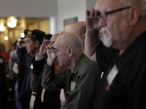 Photo - Men salute during an American Legion veterans ceremony at the Edmond Mansions retirement village in Edmond. Photos by Garett Fisbeck, The Oklahoman