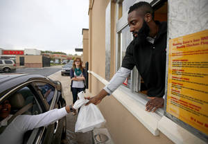 photo - James Harden of the Oklahoma City Thunder greets a customer in the drive-thru lane of the new Raising Cane's in Edmond, Thursday, September 27, 2012. Photo by Bryan Terry, The Oklahoman